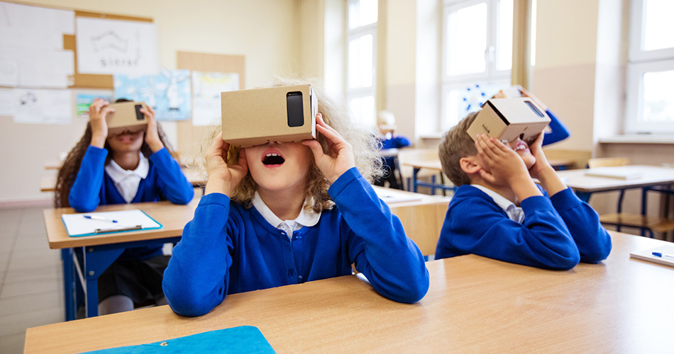 Multi ethnic group of students using virtual reality cardboard goggles in the classroom.